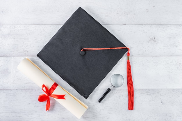 Mortarboard, magnifying glass and diploma tied with red ribbon on white wooden table, top view