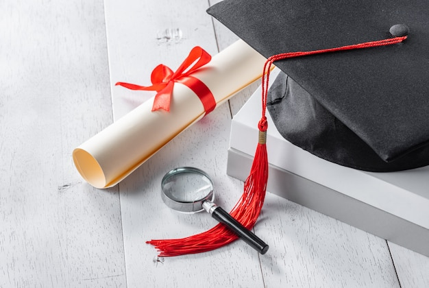 Mortarboard, magnifying glass and diploma tied with red ribbon on white wooden table