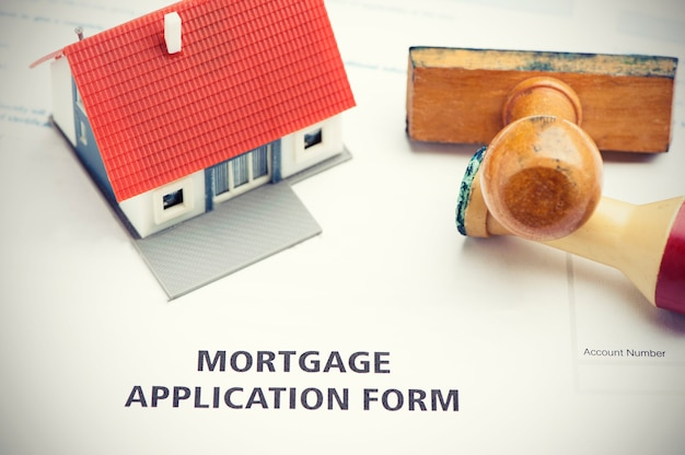 Mortgage application form with stamp and model  house
