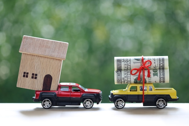 Mortgage,banknotes and model house on miniature car on nature green background, saving money for car, finance and car loan, business investment and real estate concept