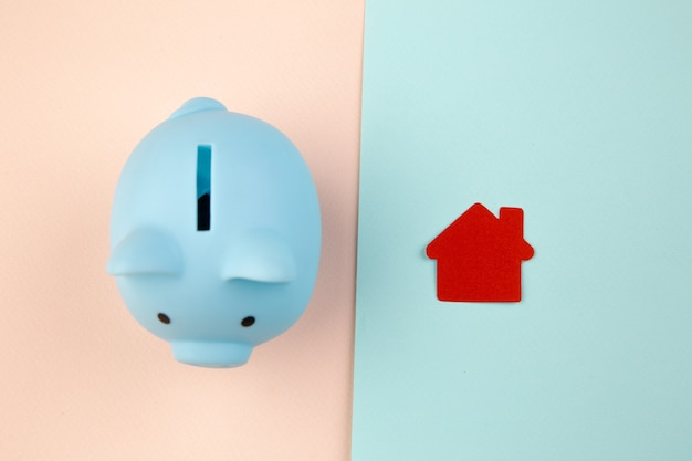 Концепция ипотеки. маленький бумажный домик рядом с копилкой.
