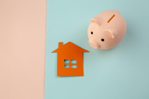Концепция ипотеки. маленький бумажный домик рядом с розовой копилкой на красочном фоне.