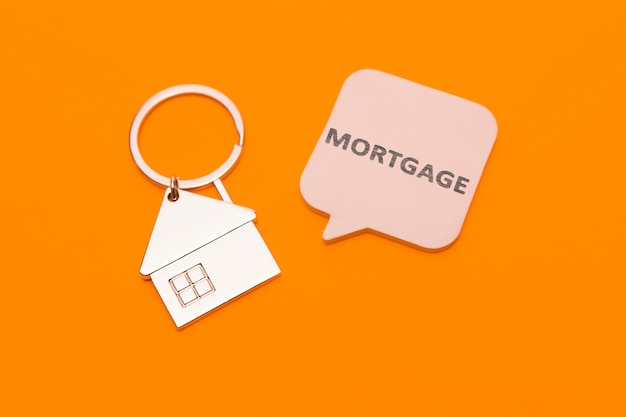 Концепция ипотеки. металлический брелок в виде дома и наклейки с надписью - ипотека на оранжевом фоне.
