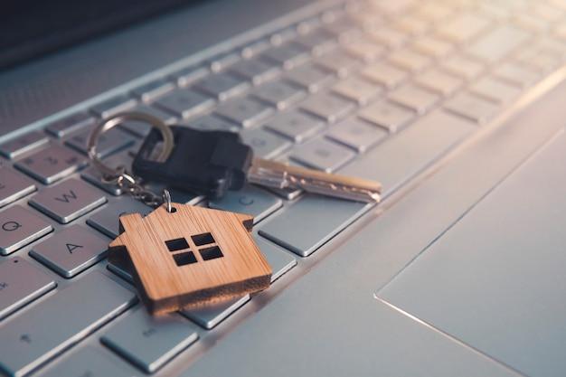 노트북 키보드에 열쇠와 집 모양의 열쇠 고리가 있는 모기지 개념. 인터넷 개념에서 꿈의 집을 찾으십시오. 주거 검색에 대한 온라인 지원. 컴퓨터 키보드에 누워 키 닫습니다.