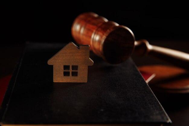 Концепция ипотеки. деревянный молоток и домик за столом.
