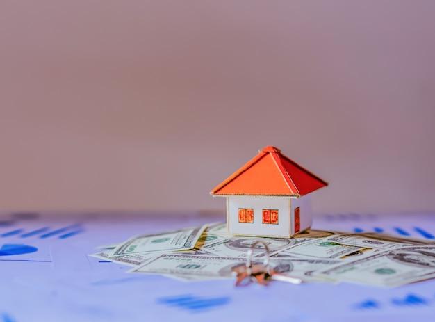 住宅ローン、投資、不動産、不動産のコンセプト - 家のモデル、ドルのお金とハウスキーのクローズアップ