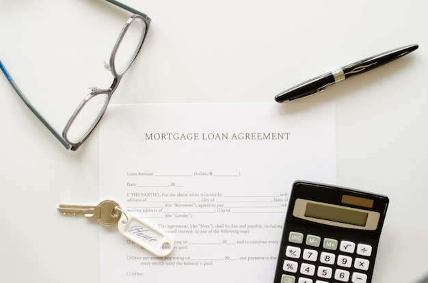 Mortgage loan agreement contract, concept with calculator, keys and pen on mortgage form or contract. top view.