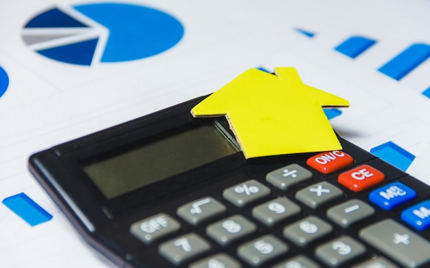 Mortgage loans concept with paper house and calculator on white background
