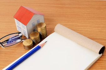 Mortgage loans concept with pencil and notepad with paper house and coins stack