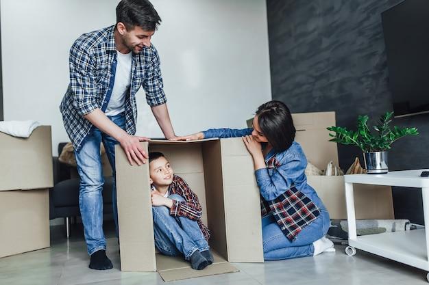 住宅ローン、人、家族、不動産のコンセプト-新しい家に移動する段ボール箱を持つ幸せな母、父と幼い息子