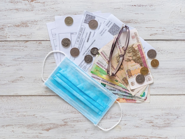 Mortgage and utility bills, coins and rubles banknotes, glasses and medical mask on wooden table.
