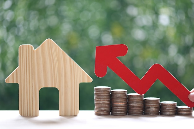Mortgage,woman hand holding red arrow graph and stack of coins money with model house on natural green background,business investment and real estate concept