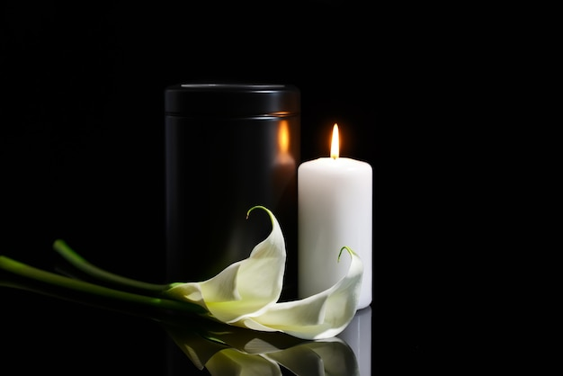 Mortuary urn, burning candle and flowers on dark background