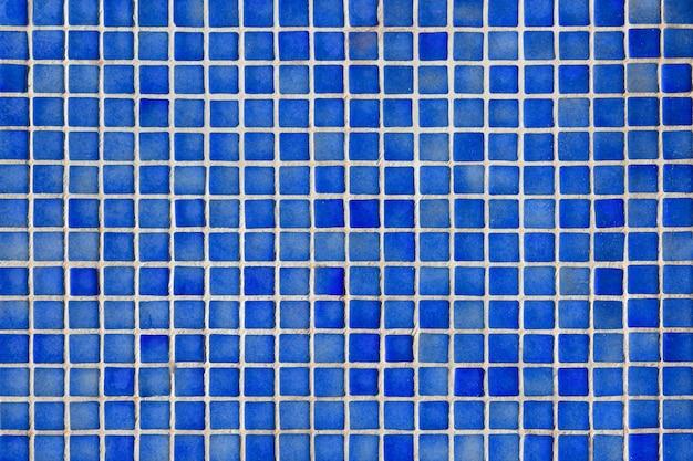 Поверхность, покрытая мозаикой, с мелкой квадратной плиткой кобальтового цвета.