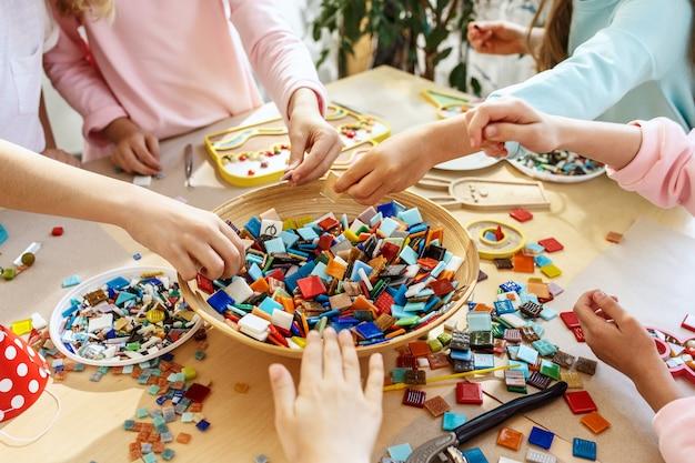 子供のためのモザイクパズルアート、子供たちの創造的なゲーム。手はテーブルでモザイクを再生しています。カラフルなマルチカラーのディテールがクローズアップ。