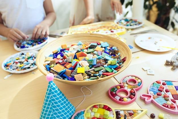 Мозаика-пазл для детей, детская творческая игра. руки играют в мозаику за столом. красочные разноцветные детали крупным планом.