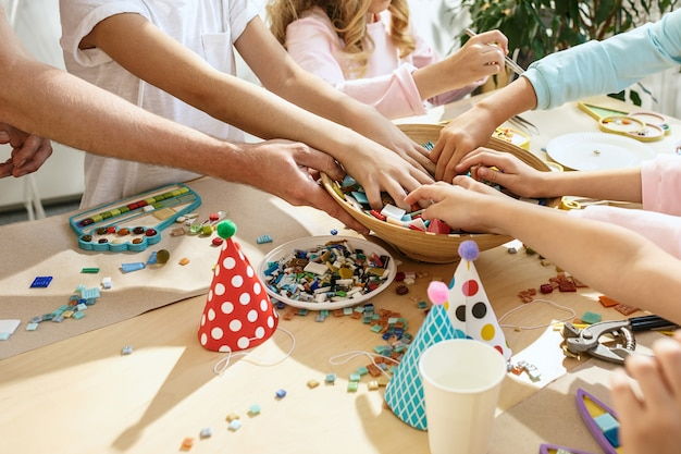 Mosaic puzzle art for kids, children's creative game. hands are playing mosaic at table. colorful multi-colored details close up.