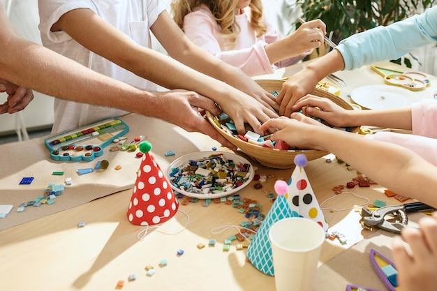 Mosaico puzzle art per bambini, gioco creativo per bambini. le mani stanno giocando a mosaico al tavolo. i dettagli multicolori variopinti si chiudono su.