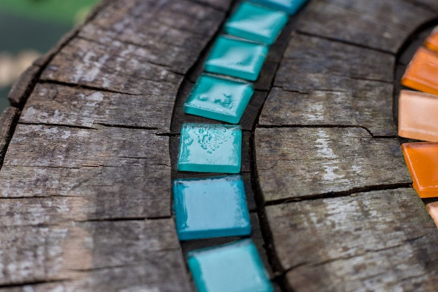 Mosaic tiles on round cut down tree with cracks stump outside macro. diy garden furniture, decorated by hand made element small tiles. mosaic color path in rain. abstract natural wooden background.