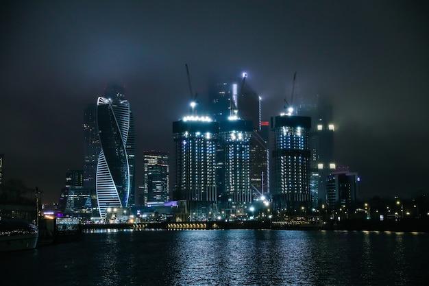 Здание москва-сити в ночном представлении с москвы-реки. москва, россия.