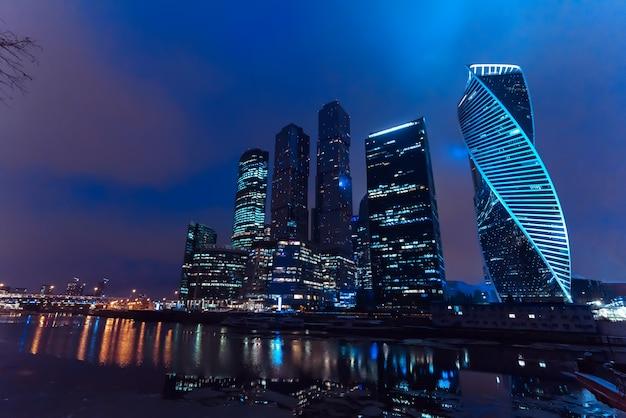 夜のロシアの首都で川沿いのモスクワ市の超高層ビルタワー