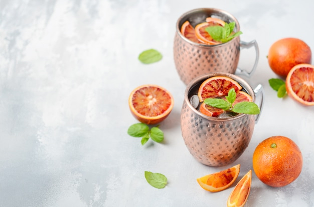 Moscow mule cocktail with fresh mint leaves and ice in copper mugs
