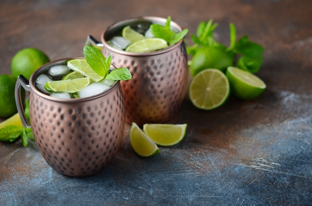 Moscow mule cocktail with ginger beer, vodka, lime and mint in a cooper mugs