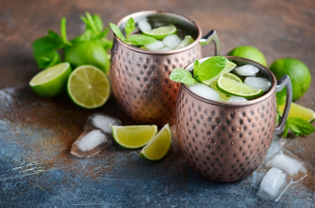 Moscow mule cocktail with ginger beer, vodka, lime and mint in a copper mugs
