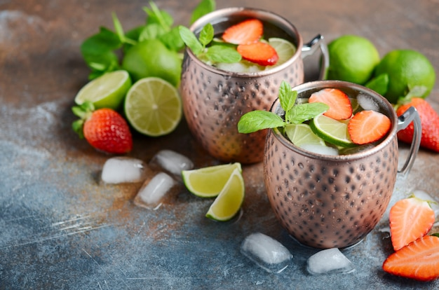 Moscow mule cocktail with ginger beer, vodka, lime, strawberries and mint in a copper mugs