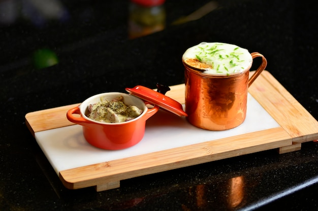 レモン、生姜、肉の前菜が入った小さな鍋が入ったモスコミュールドリンクマグ