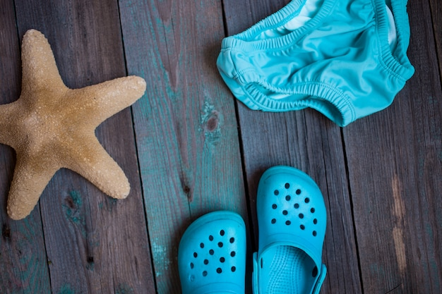 Moscow, russia - 05.28.2018: baby beach slippers, starfish, baby swimming trunks on wooden background
