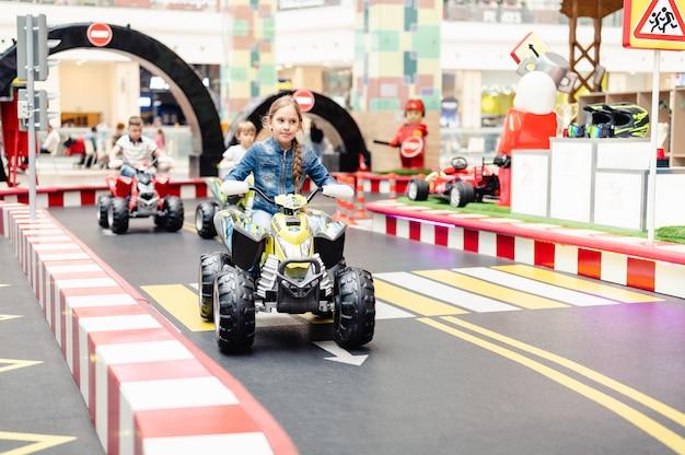 Москва, россия, 28 мая 2021 года - маленькая счастливая девочка весело катается на небольших электромобилях на спортивной площадке на игровой площадке для развлечений. дети катаются на игрушечном автомобиле в парке развлечений
