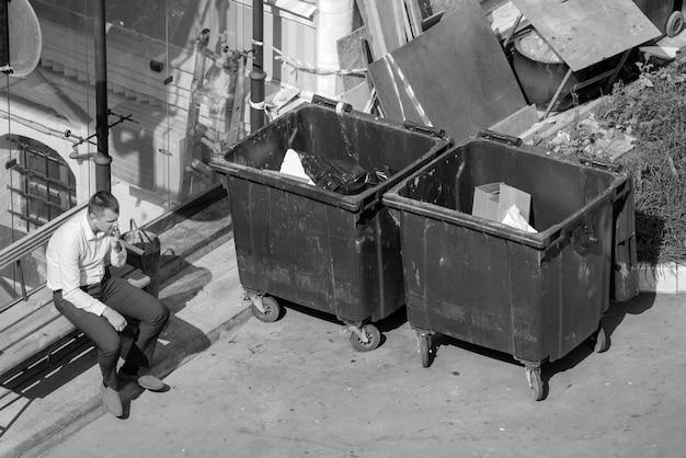 Москва, россия. 31 августа. 2021 год. мужчина курит, сидя возле мусорных баков.
