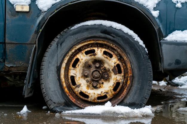 ロシアのモスクワ。冬の雪の中で古い車のパンクしたタイヤ。