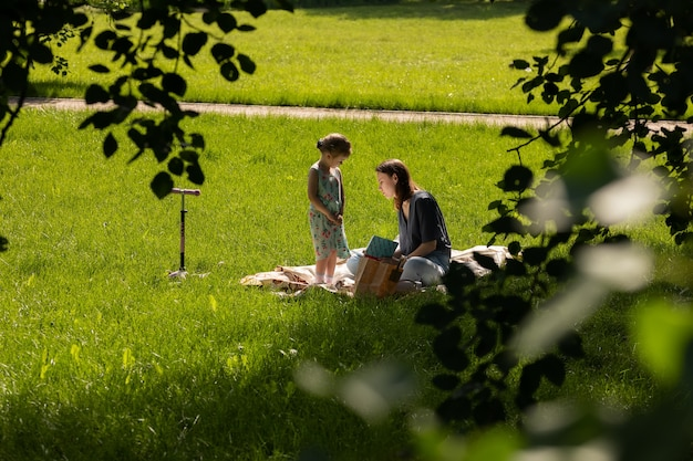 モスクワ/ロシア-2020年6月:草の上に座って本を読んでいる母と娘