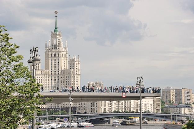 モスクワ、ロシア-2021年6月6日:モスクワのザリャディエ公園のコテリニチェスカヤ堤防と浮き橋の高層ビルの眺め