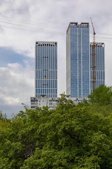 모스크바 / 러시아-2020 년 5 월 : 흐린 하늘을 배경으로 주거 단지 건설 작업을하는 lconstruction 크레인이있는 대형 건설 현장