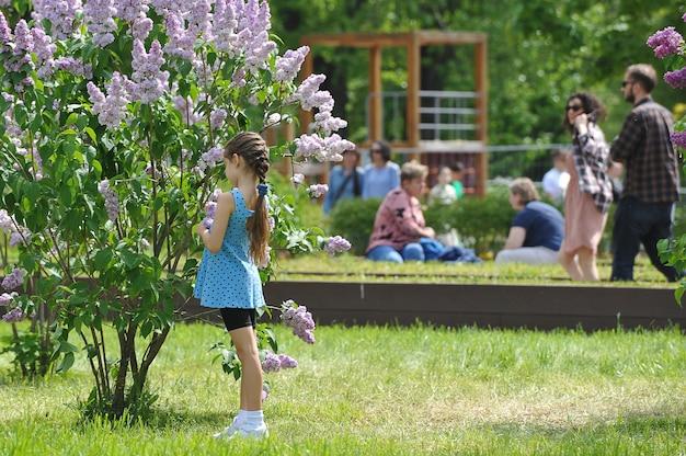 모스크바, 러시아 - 2021년 5월 23일: 어린 소녀가 모스크바의 공원에서 라일락을 바라보고 있습니다.