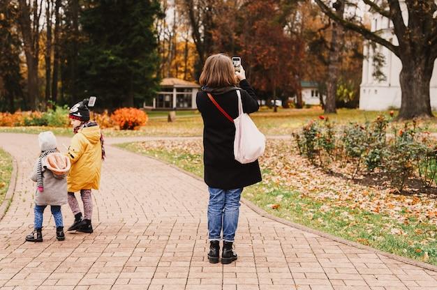 모스크바, 러시아, 2019년 10월 - 여행자 어머니가 스마트폰으로 가을 공원의 풍경을 촬영합니다. 그녀의 아이들이 근처를 걷고 있습니다. 지역 가족 여행 컨셉입니다. 뒷모습, 뒤