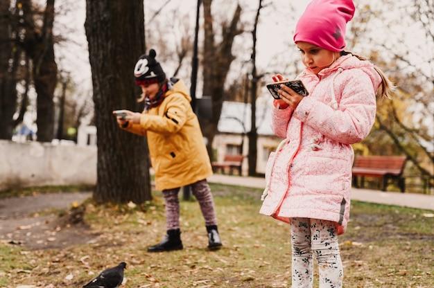 모스크바, 러시아, 2019년 10월 - 여행자 작은 자매 아이들이 가을 공원에서 산책하는 동안 스마트폰으로 오리가 있는 풍경과 연못의 사진을 찍습니다. 현지 가족 여행 컨셉