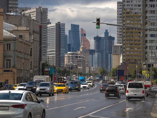 車のモスクワの交通。雨の夏の日のノヴィアルバートストリート。