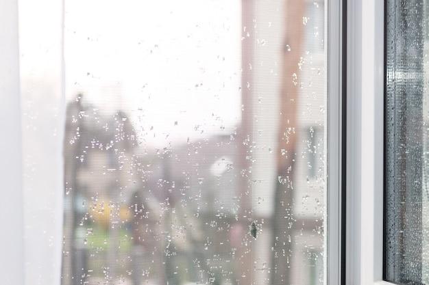 Москитная сетка в пластиковой оконной раме после дождя