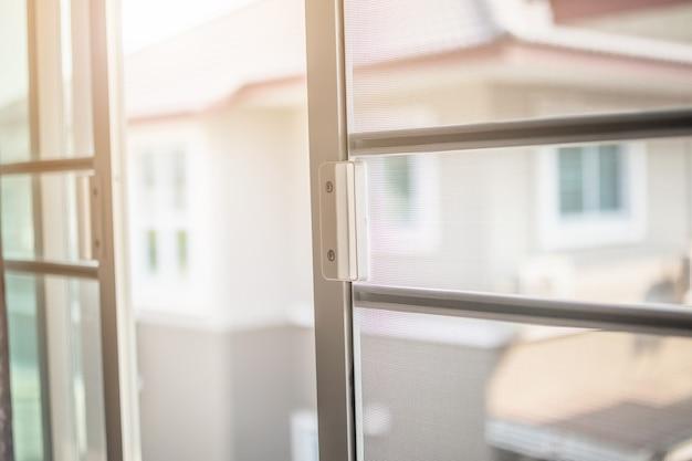 Экран из проволоки москитной сетки на окне дома для защиты от насекомых