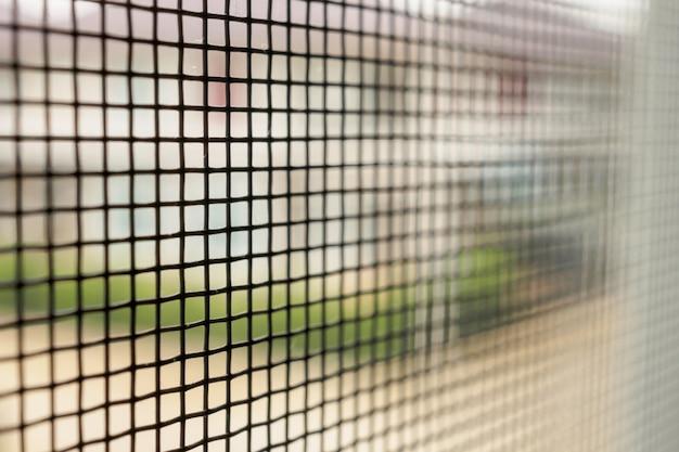Экран из проволочной сетки от комаров на окне дома для защиты от насекомых