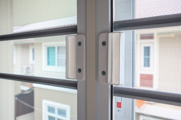 Экран из проволоки москитной сетки на окне дома для защиты от насекомых Premium Фотографии