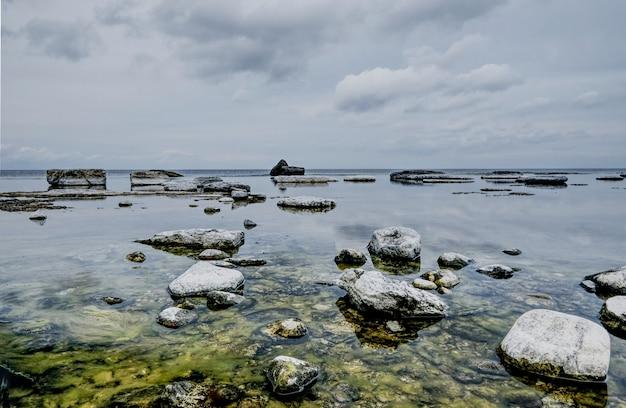 曇り空の下で湖の苔むした岩