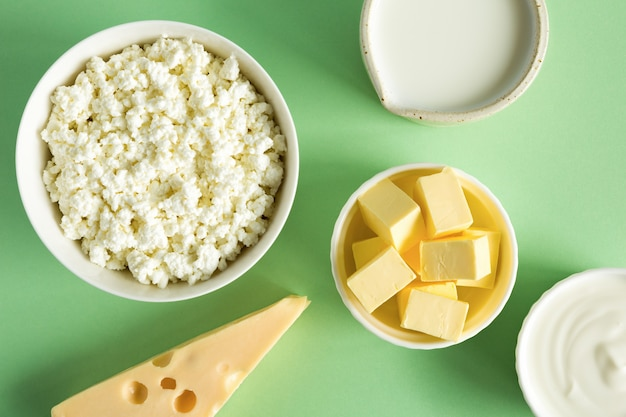 牛乳からの最も一般的な製品は、バター、チーズ、牛乳、サワークリーム、緑の紙の背景のフラットレイのカッテージチーズです。自然の有機食品。強い骨のための食品。