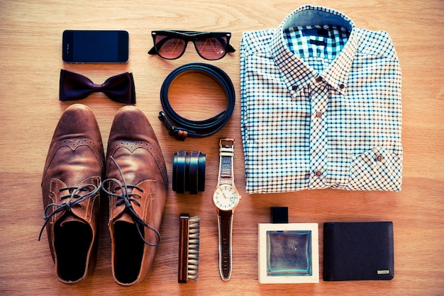 The most important things. top view of clothing and diverse personal accessory laying on the wooden grain