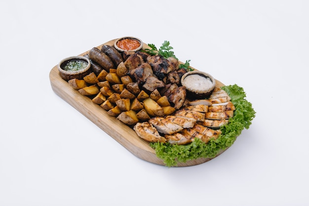 Большинство мясных блюд - шашлыки из говядины, сосиски, грибы-гриль, картофель, помидоры и соус. лучший выбор к пиву. крупный план.