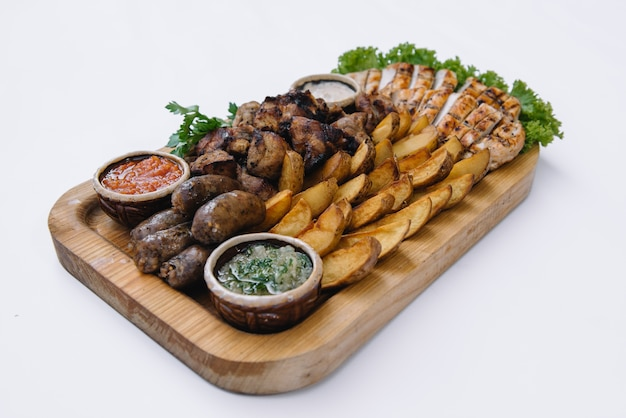 Most meat dish - beef kebabs, sausages, grilled mushrooms, potatoes, tomatoes and sauce. the best choice for a beer. close-up.